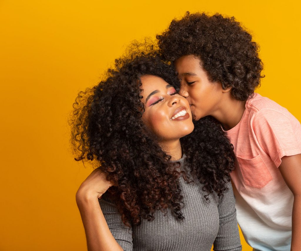 portrait-young-african-american-mother-with-toddler-son-son-kissing-his-mother-yellow-wall-brazilian-family