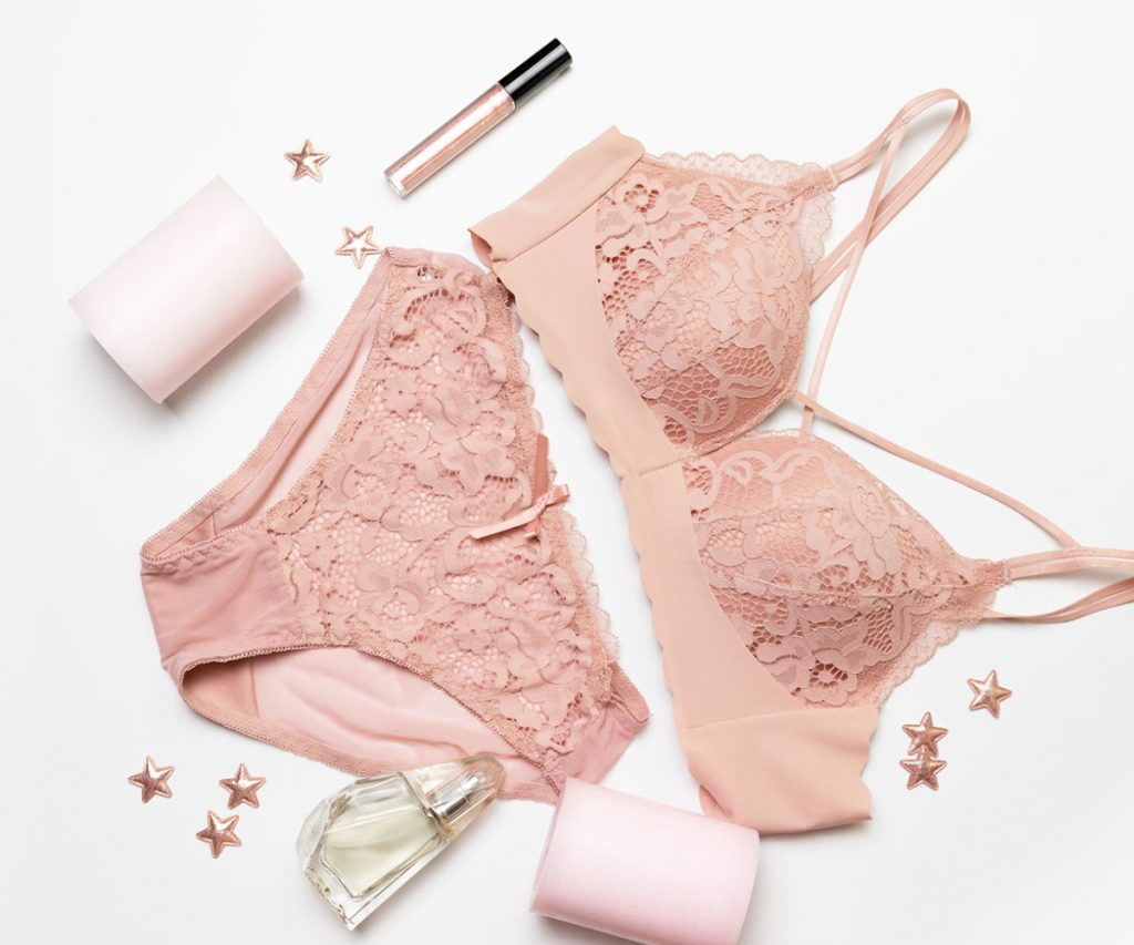 romantic-composition-with-female-pink-underwear-candle-lip-gloss-perfume-stars